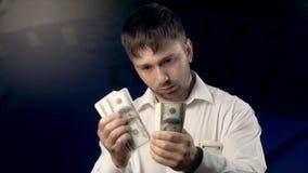 Porträt des ernsten jungen Mannes, der einige Dollar aus seiner Tasche heraus erhält stock footage