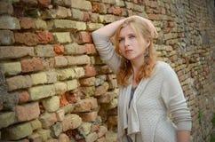Porträt des ernsten Mädchens nahe einer Backsteinmauer, Lizenzfreies Stockfoto