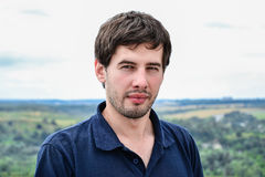Porträt des ernsten zufälligen jungen Mannes gegen Landschaft Stockbild