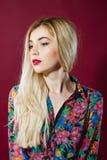 Porträt des erstaunlichen blonden Modells mit dem langen Haar im bunten Hemd und im Weiß-Rock auf rosa Hintergrund Sinnliches jun Stockbilder