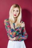 Porträt des erstaunlichen blonden Modells mit dem langen Haar im bunten Hemd und im Weiß-Rock, welche die Kamera auf Rosa betrach Stockfotos
