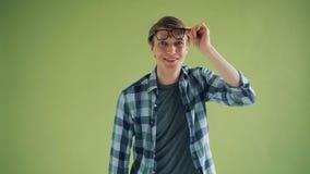 Porträt des erstaunten jungen Mannes, der die Gläser betrachten Kamera und das Lächeln anhebt stock video
