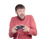 Porträt des erwachsenen bärtigen Mannes, der Steuerknüppel hält und Videospiele, lokalisiert auf weißem Hintergrund spielt stockbilder