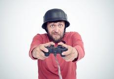 Porträt des erwachsenen bärtigen Mannes im Sturzhelm, der Steuerknüppel hält und Videospiele spielt lizenzfreie stockfotografie
