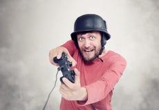 Porträt des erwachsenen bärtigen Mannes im Sturzhelm, der Steuerknüppel hält und Videospiele spielt lizenzfreies stockbild