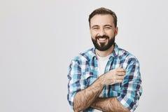 Porträt des erwachsenen bärtigen Mannes mit glänzendem Lächeln und den gekreuzten Händen, Kamera, über grauem Hintergrund betrach Lizenzfreies Stockbild