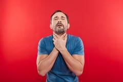 Porträt des erwachsenen bärtigen Mannes 30s, der schmerzliche Halsschmerzen hat und lizenzfreie stockbilder
