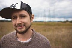 Porträt des erwachsenen mutigen jungen Mannes auf Wiese, Energiemasten am Hintergrund Lizenzfreie Stockfotos
