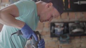 Porträt des Fähigkeitsvorlageningenieurs gerichtet auf die Bohrung eines Lochs mit Werkzeug auf dem Hintergrund einer kleinen Wer stock footage