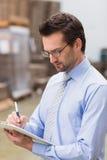 Porträt des fokussierten Managerschreibens auf seinem Klemmbrett Stockbild