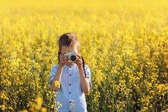 Porträt des Fotografen des kleinen Jungen mit Kamera auf gelborangem Feldhintergrund Lizenzfreies Stockfoto