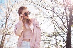 Porträt des Frühlingsmode-Mädchens draußen in blühenden Bäumen Romantische Frau der Schönheit in den Blumen in der Sonnenbrille S lizenzfreie stockbilder