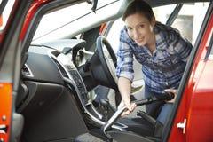 Porträt des Frauen-Reinigungsinnenraums des Autos unter Verwendung des Staubsaugers lizenzfreies stockfoto