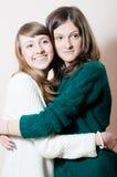 Porträt des freundlichen Umarmens von zwei jungen attraktiven entzückenden Frauen in den Strickwaren Lizenzfreies Stockfoto