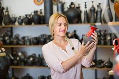 Porträt des frohen Frauenwählens glasiert mit rote Farbekeramischem ut lizenzfreie stockbilder