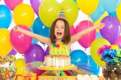 Porträt des frohen kleinen Mädchens mit Kuchen an Stockfotografie