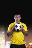 Porträt des Fußballspielers einen Fußball, Hintergrund halten nachts lizenzfreies stockbild
