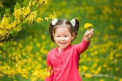Porträt des funy kleinen Mädchens mit gelbem Löwenzahn in der Hand Stockbild