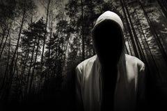 Porträt des gefährlichen Mannes unter der Haube im Wald Stockfoto