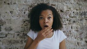 Porträt des gelockten Afroamerikanerjugendlichmädchens aktiv, das auf Backsteinmauerhintergrund überraschend und gewundert worden lizenzfreie stockfotos