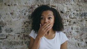 Porträt des gelockten Afroamerikanerjugendlichmädchens aktiv, das auf Backsteinmauerhintergrund überraschend und gewundert worden stockfotos