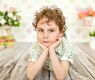 Porträt des gelockten braunäugigen Jungen in einem hellen beige Kleid Stockfotografie