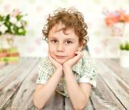 Porträt des gelockten braunäugigen Jungen in einem hellen beige Kleid Stockbilder