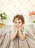 Porträt des gelockten braunäugigen Jungen in einem hellen beige Kleid Lizenzfreie Stockbilder