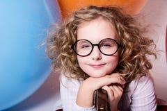 Porträt des gelockten jugendlich Mädchens mit verengten Augen auf dem Hintergrund Stockfotos