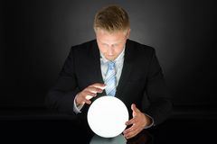 Porträt des Geschäftsmannes mit Glaskugel Stockfotografie