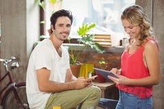 Porträt des Geschäftsmannes mit intelligentem Telefon während Frau, die digitale Tablette im Büro verwendet Stockbilder