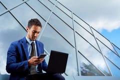 Porträt des Geschäftsmannes mit Laptop, sprechend am Handy B stockfotos