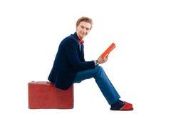 Porträt des Geschäftsmannes sitzend auf seinem Koffer während und Lächeln Stockbild