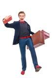 Porträt des Geschäftsmannes sitzend auf seinem Koffer während und Lächeln Stockfotografie