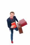Porträt des Geschäftsmannes sitzend auf seinem Koffer während und Lächeln Stockfotos