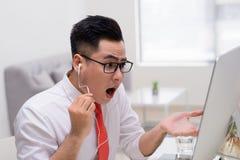 Porträt des Geschäftsmannes sitzend am Schreibtisch und Video habend stockfoto