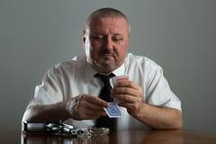 Porträt des Geschäftsmannrauchen und -spielpokers lizenzfreie stockfotos