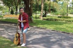 Porträt des Gitarristen entspannend gegen Akustikgitarre in der Natur mit Kopienraumhintergrund Lizenzfreie Stockfotografie