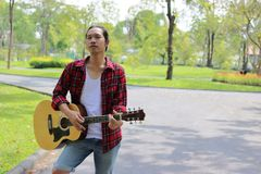 Porträt des Gitarristen Musik auf Akustikgitarre im Parkhintergrund spielend Stockfotos