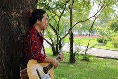Porträt des Gitarristen oder des Musikers spielt Akustikgitarre im schönen Naturparkhintergrund Lizenzfreie Stockfotos