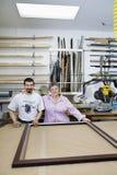 Porträt des glücklichen älteren Inhabers mit reifem Angestelltem in der Rahmenwerkstatt Stockfotografie