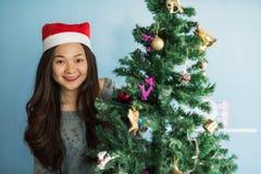 Porträt des glücklichen asiatischen chinesischen Mädchens mit Santa Claus-Hut feiern Weihnachten nahe Weihnachtsbaum, um Feiertag stockfotos