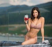 Porträt des glücklichen attraktiven Mädchens mit perfektem Körper im Bikini, der am Jacuzzi mit Cocktail sitzt Stockfotografie