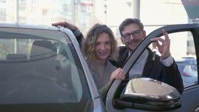 Porträt des glücklichen Autokäufers, junge Paarliebhaber erfreuen neues Fahrzeug und Darstellenschlüssel im Selbstsalon stock video