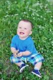 Porträt des glücklichen Babys sitzend auf der Wiese Stockbild