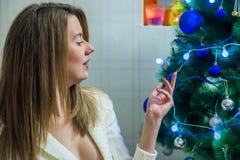 Porträt des glücklichen entspannenden nahen Weihnachtsbaums der jungen Frau Lächelnde junge Frau Lizenzfreie Stockfotos