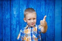 Porträt des glücklichen frohen schönen kleinen Jungen, der Daumen AG gestikuliert Stockbilder