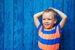 Porträt des glücklichen frohen schönen kleinen Jungen gegen die alte Querstation Stockfotos