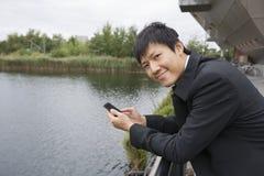 Porträt des glücklichen Geschäftsmannes mit dem Handy, der auf Brückengeländer sich lehnt Stockfotografie