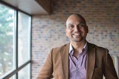 Porträt des glücklichen hübschen indischen Geschäftsmannes, zuhause lächelnd, überzeugt und freundlich lizenzfreies stockfoto